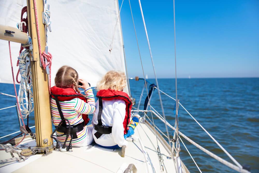 Kinder mit Sicherheitswesten auf einem Segelboot
