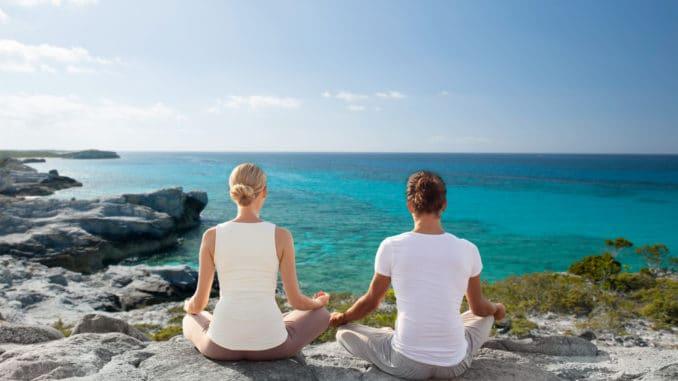 Pärchen macht Yoga in Spanien am Strand