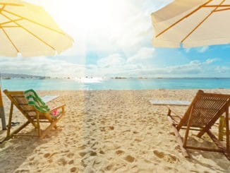 2 Stühle und Sonnenschirme am Strand