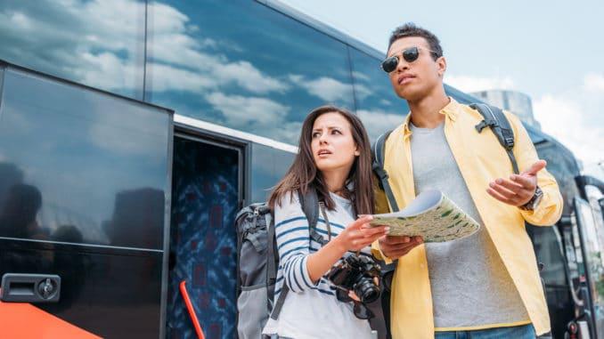 Junges Paar vor Reisebus
